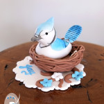 Personalised Naming Day cake topper: Baby Blue Jay bird in nest with branches and flowers. Entirely edible and painted by hand to resemble a real Blue Jay. See blog post for more.