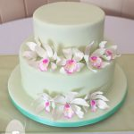 Carrot cake, white chocoloate mud cake, and edible Cymbidium orchids on a mint green fondant covering. Gympie wedding reception at Kingston House Impressions.
