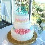 Pastel chevrons, icing roses, and a glittering gold baseboard. Choc-hazelnut, lime & coconut, and rich chocolate cake made up the three tiers of this Rainbow Beach wedding cake, with fun toppers supplied by the gorgeous bride and groom.