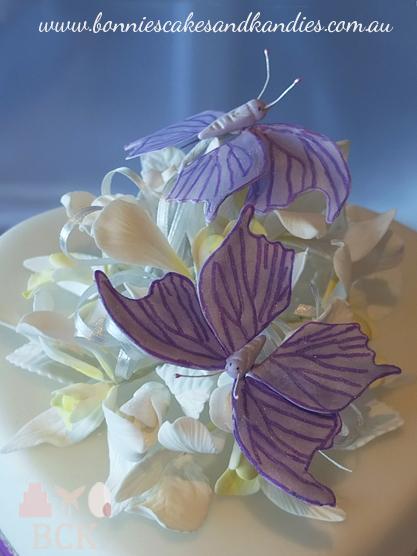 Purple butterfly wedding cake for a Mackay wedding:- traditional fruit cake with royal purple ribbon, white puffed hearts, butterflies, diamontes, white rosebuds, white Singapore orchids, two large purple butterflies - Bonnie's Cakes & Kandies, Gympie, Rainbow Beach & Sunshine Coast wedding cake decorator. The top tier was a heart shape, with the back of the heart raised approximately 2 inches, and the point of the heart almost touching the bottom tier, which was a square shape.