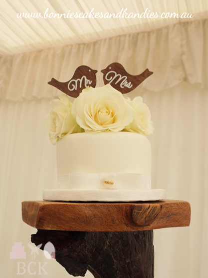 Dark chocolate mud cutting cake with white chocolate fondant, beautiful fresh roses and wooden lovebird cake topers  |  Bonnie's Cakes & Kandies, Gympie.
