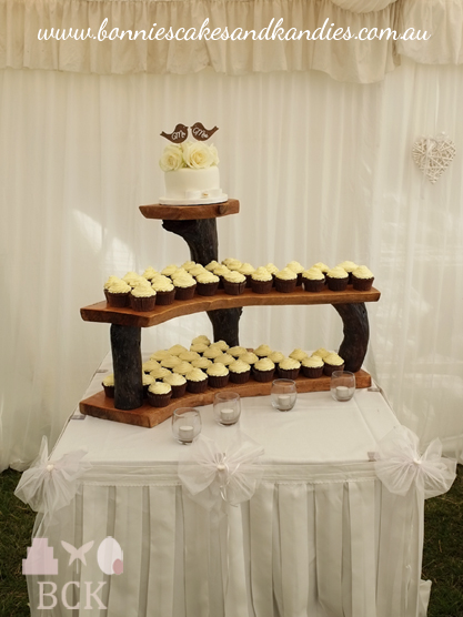 Chocolate cupcakes with white chocolate buttercream icing, arranged underneath a dark chocolate mud cutting cake on a beautiful, rustic timber stand |  Bonnie's Cakes & Kandies, Gympie.
