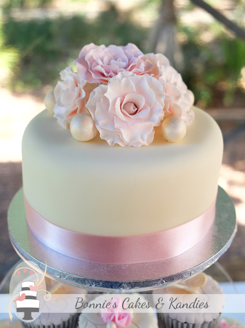 A posy of frilled rose-like fantasy flowers and edible pearls decorated the cutting cake  |  Bonnie's Cakes & Kandies