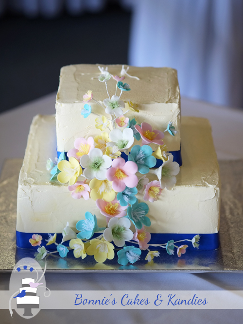 Vanilla sponge & banana cake with a white chocolate buttercream covering, and icing flowers coloured to suit a spring theme|  Bonnie's Cakes & Kandies