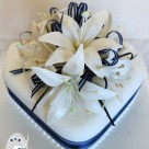 Two tier offset square wedding cake with navy ribbon and white lilies Bonnies Cakes and Kandies Gympie Noosa Rainbow Beach Montville Maleny Kenilworth Cake Decorator