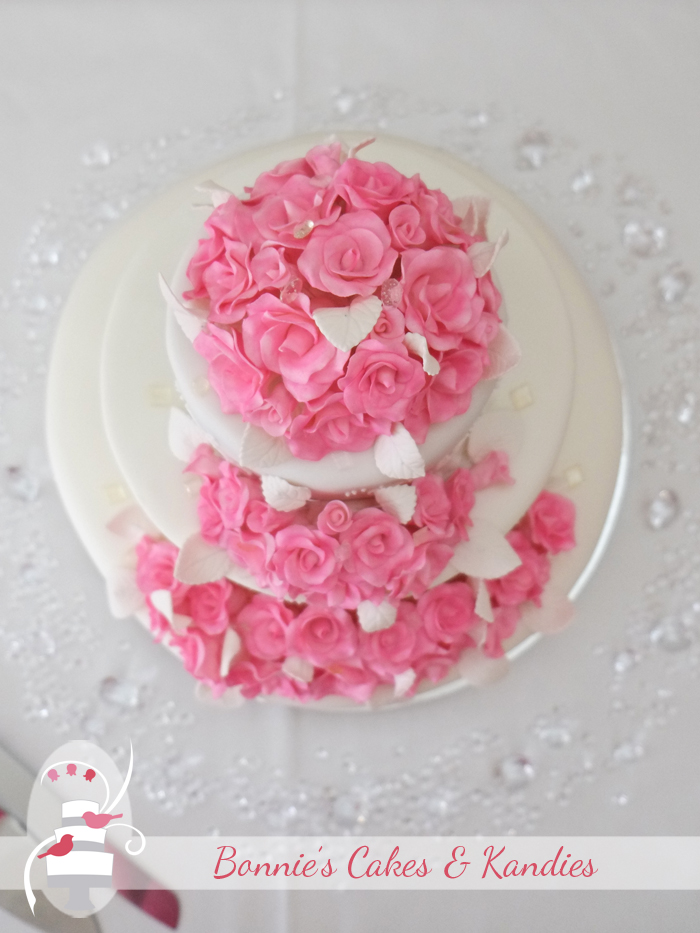 Pink roses on white wedding cake for a Rainbow Beach wedding reception