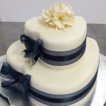 Elegant heart-shaped ivory navy wedding cake frangipani flowers Bonnies Cakes Kandies Gympie