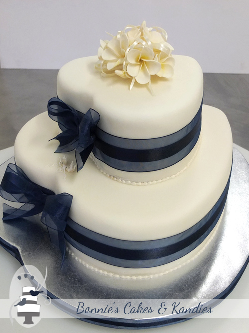 Elegantly decorated with navy ribbon and bows and icing flowers  |  Bonnie's Cakes & Kandies