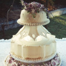 "More 'vintage' than 'modern-vintage' this wedding cake features string work, a collar with 4"" high extension work, large purple flowerpaste roses and an upside down crown or lamp-shade effect 
