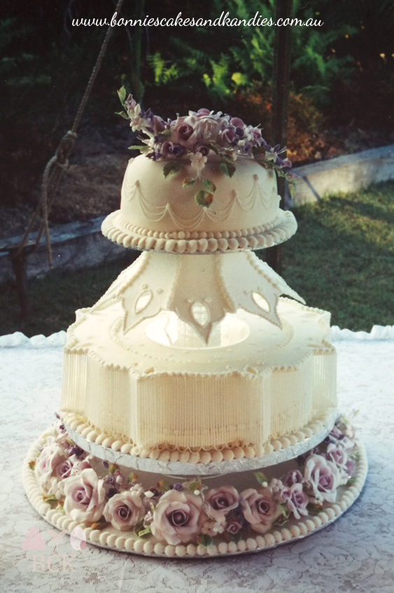 "More 'vintage' than 'modern-vintage' this wedding cake features string work, a collar with 4"" high extension work, large purple flower paste roses and an upside down crown or lamp-shade effect  