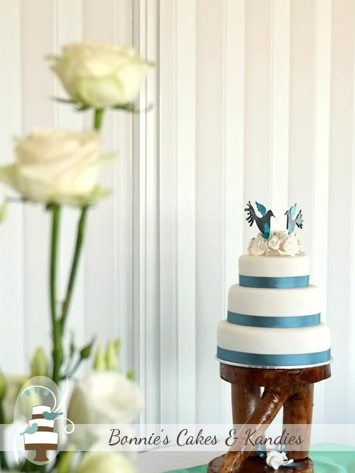 Three tier Rainbow Beach wedding cake, presented on a custom-made wooden cake stand  |  Bonnie's Cakes & Kandies