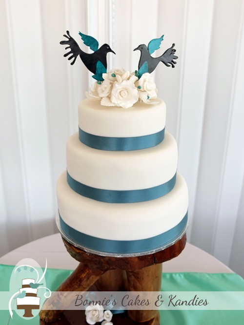 Traditional fruit cake with white icing roses and lovebird cake toppers for a Rainbow Beach wedding     Bonnie's Cakes & Kandies