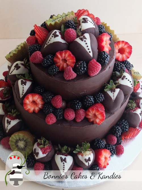White chocolate mud cake and chocolate fudge cake, covered in deliciously decadent dark chocolate ganache, and decorated with strawberries, kiwi fruits, blueberries, blackberries and raspberries  |  Bonnie's Cakes & Kandies, Gympie