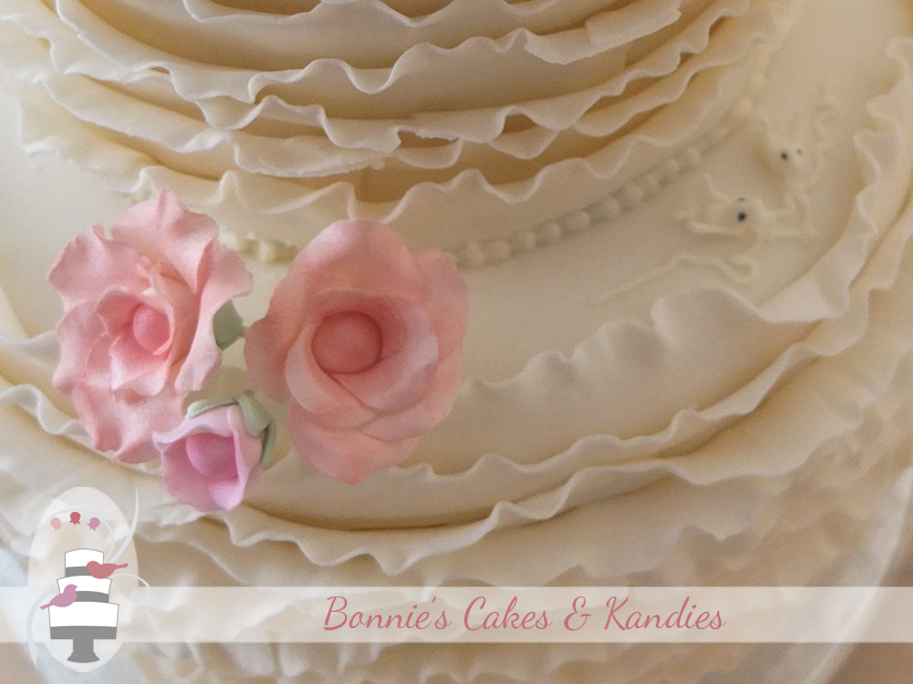 Frilled rose-like fantasy flowers were made in shades of pink to match with the bridesmaid dresses – Bonnie's Cakes & Kandies, Gympie