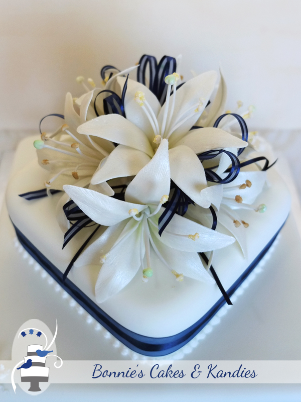 A posy of white lilies with navy blue ribbon - Gympie Wedding Cake Decorator